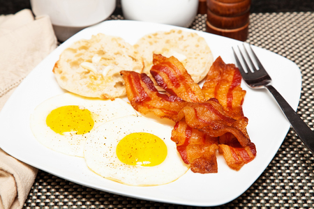 bacon and eggs: Plate of breakfast including two fried eggs, bacon and an english muffin