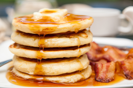 bacon: A tall stack of pancakes with butter and dripping syrup and three strips of bacon
