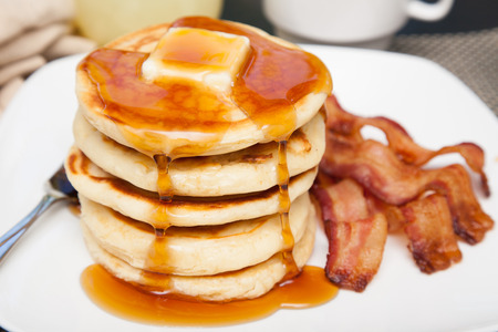 maple syrup: A tall stack of pancakes with butter and dripping syrup and three strips of bacon