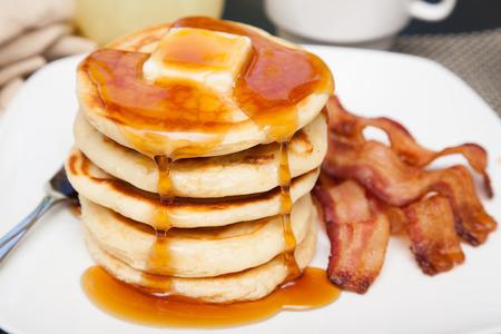 Ein großer Stapel von Pfannkuchen mit Butter und tropfte Sirup und drei Streifen Speck Standard-Bild - 47230315