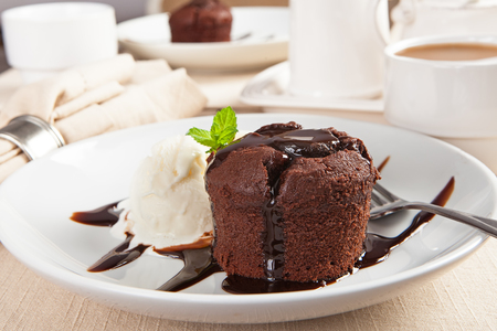 vanilla pudding: Delicious molten chocolate lava cake with vanilla ice cream on table with coffee and second dessert in background Stock Photo