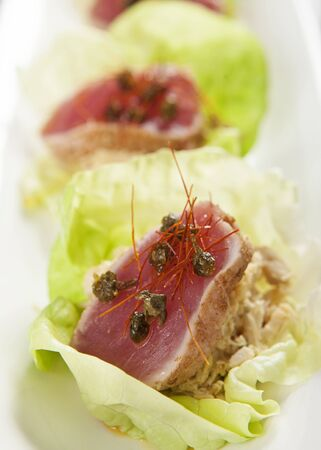 ahi: Healthy appetizer of fresh seared ahi tuna resting in pieces of romaine lettuce Stock Photo