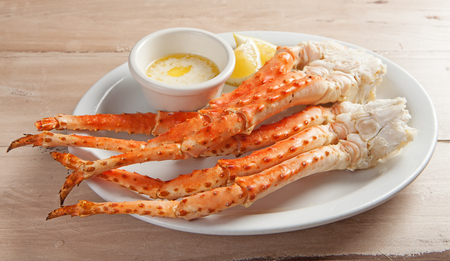 Clusters of fresh snow crab legs on a white plate resting on a wood table with melted butter and lemon Stock Photo