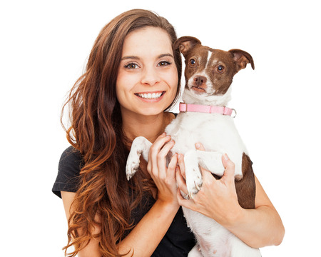 looking into camera: Portrait of a pretty young brunette woman holding a little mixed breed dog. Both are looking into camera.
