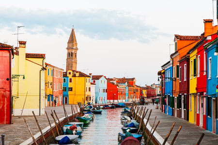 bright colors: Street scene of colorful houses and boats along a waterway in the village of Burano in Venice, Italy