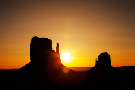 tribal park: Golden sunrise silhouette of mitten buttes in Monument Valley National Park on the border of Arizona and Utah, USA