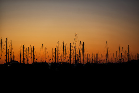 masts: Silhouette of a row of sail masts docked at a harbor in California in the morning with a colorful orange sunrise Stock Photo