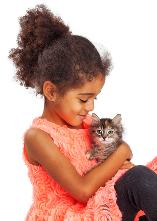 and four of the year: Happy and smiling mixed race four year old girl holding a kitten Stock Photo