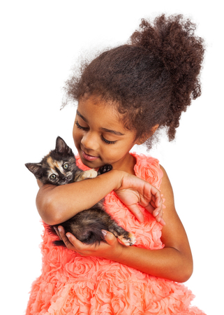 and four of the year: Pretty four year old multicultural girl holding and looking at a kitten