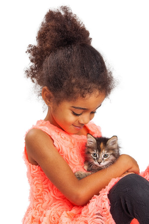 and four of the year: Happy mixed race four year old girl holding a kitten and looking down at it Stock Photo