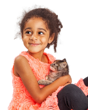 and four of the year: Happy mixed race four year old girl holding a kitten and looking up with a smile