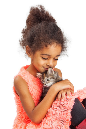 and four of the year: Heartfelt photo of a four year old girl holding a kitten and closing her eyes while smiling Stock Photo