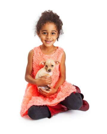 and four of the year: Pretty four year old mixed race girl with happy expression holding a Chihuahua puppy