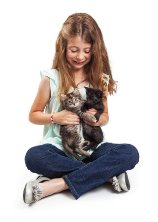 Eight year old girl holding two little kittens. Isolated on white.