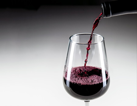 pinot noir: Closeup of red wine being poured into glass with copy space