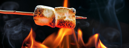 Two marshmallows roasting over fire flames. Sized to fit popular social media horizontal banner Foto de archivo