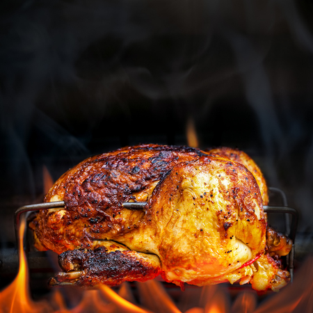 grill chicken: Charred rotisserie chicken over open flames in a barbecue. Square format with room for text