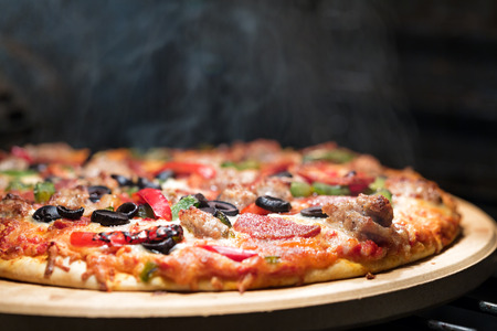 Hot supreme thin crust pizza cooking in oven with steam and smoke Foto de archivo