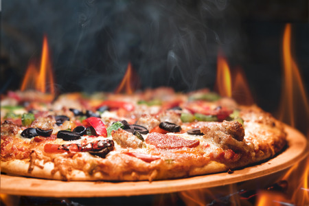 Supreme meat and vegetable pizza on stone in wood-fired oven with open flames Imagens