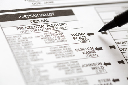 absentee: PHOENIX, AZ - OCTOBER 21, 2016: Close up of a pen about to mark the 2016 USA general election early voting ballot form with a vote for Donald Trump as president.