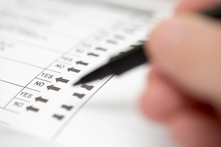 other keywords: Selective focus on Yes or No options on an election ballot with a blurred hand holding a marker to cast a vote