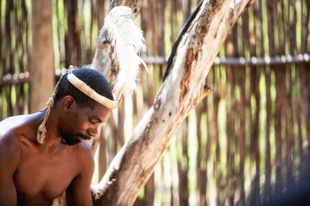 LESEDI CULTURAL VILLAGE, SOUTH AFRICA - NOVEMBER 4, 2016. Candid profile portrait of a young male tribal warrior wearing a traditional feather headdress as he works to entertain tourists