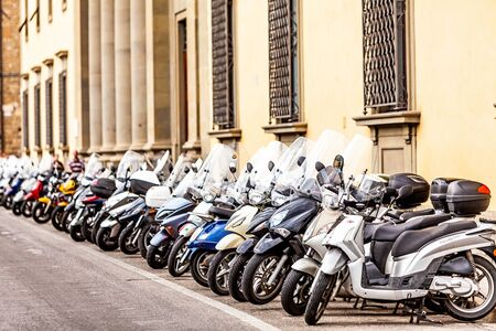 parked bikes: Florence, Italy - September 21, 2012. A row of motor bikes parked along the Ponte Vecchio bridge in Florence, Italy. Scooters and motorbikes are a common transportation rental option for tourists.