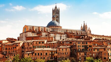 View of building in center of Siena, Italy with Cathedral of Santa Maria Assunta in background Stock Photo