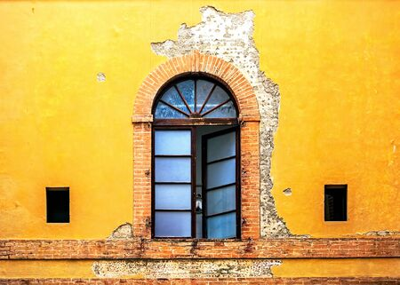 Open window and outside weathered facade of colorful yellow home in Siena Italy Stock Photo - 71190290