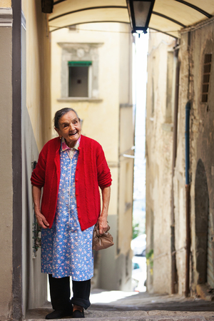 Cortona, Italy - September 20, 2012. Unidentified elderly Italian woman with a friendly smile appears in a corridor in the small hill town of Cortona to greet tourists, greet, welcome. 新聞圖片