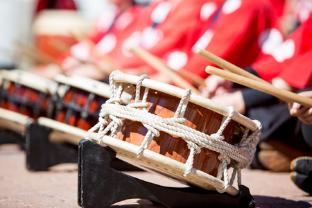 Row of Japanese taiko drums lined up with people playing them. Selective focus on first drum.