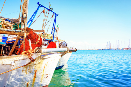 Closeup of two fishing boats docked at a harbor in Trapani, Sicily, Italy