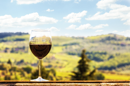 A glass of red Chianti wine resting on the ledge of a patio outdoors with the beautiful Italian countryside in the region of Tuscany 新聞圖片