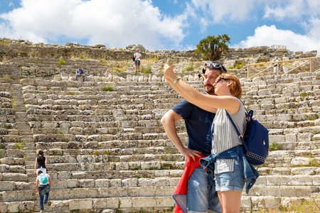 Segesta, Sicily, Italy - May 20, 2017: Tourists visit the popular historic site in Segesta, Sicily with ruins of the amphitheater, taking selfies with a cell phone Redakční