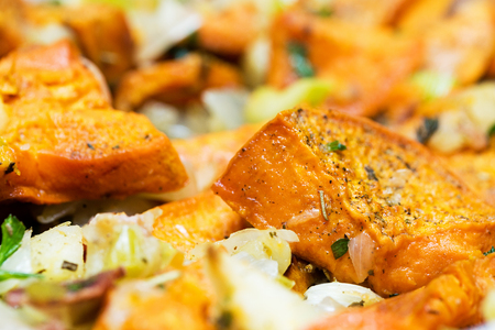 Healthy vegetable side dish of roasted sweet potatoes, bacon, apple, celery, onion and herbs Stock Photo