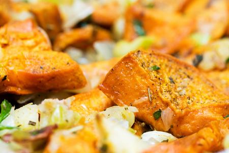 Healthy vegetable side dish of roasted sweet potatoes, bacon, apple, celery, onion and herbs Фото со стока