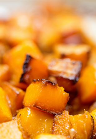 Closeup selective focus photo of fresh seasonal butternut squash cut up into cubes and roasted with olive oil and salt