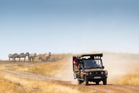 Masai Mara, Kenya, Africa - July 29, 2017: Safari tourists view herds of zebra during migration season in the Mara Triangle region of Kenya