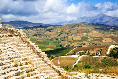 View of part of the amphitheater ruins on top of a hill overlooking the beautiful city of Segesta in Sicily, Italy