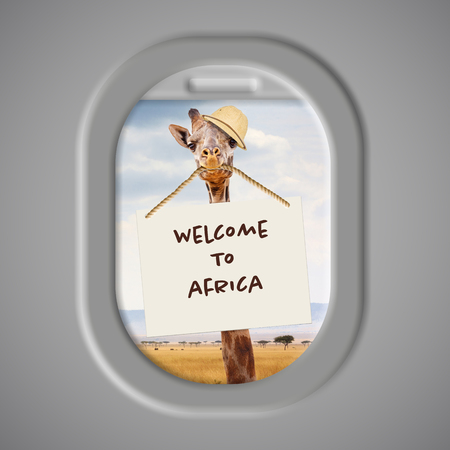 Funny photo of giraffe wearing safari hat and holding Welcome to Africa sign in mouth with Kenya landscape in background