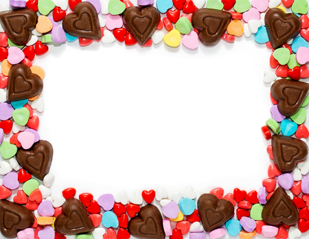 Assorted Valentines Day candy around border of white letter size paper