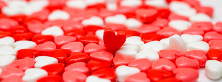 Bunch of heart shaped Valentines Day candies with selective focus on one that is sticking up