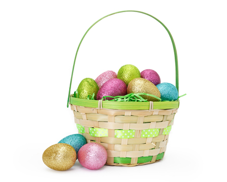 Wicker Easter basket filled with colorful glitter covered eggs. Isolated on white.