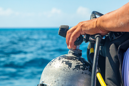 Closeup of the hand of a scuba diver on the nozzle of an oxygen tank on a boat with ocean water in background 写真素材