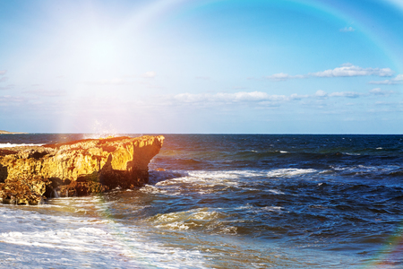 Waves crashing against rocks on the shore of the Caribbean Sea in Cozumel Mexico with colorful rainbow sun flare Stock Photo