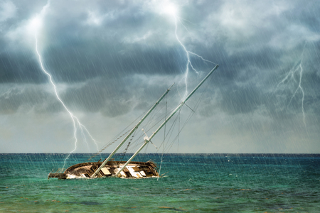 Shipwrecked sailboat in a tropical lightning storm on the Caribbean Sea in Mexico Stock Photo