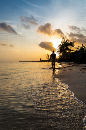 Silhouette of a man walking down the shore of a beautiful beach in Cozumel, Mexico during early morning sunrise Stock Photo