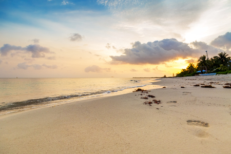 Foot prints in the sand along the shore of a beach on the Caribbean Sea in Cozumel, Mexico at sunrise