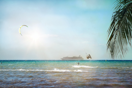 Kite surfers on beach in Cozumel, Mexico with palm tree leaves and cruise ship Stock Photo