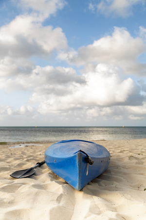 Blue kayak boat on a sandy beach in Mexico with room for text in sky